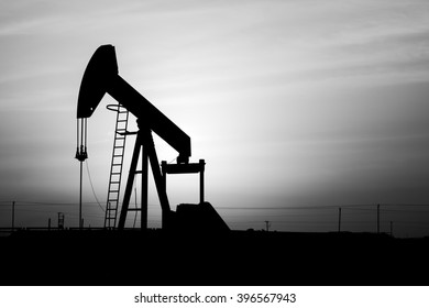 Cloudy sunset and silhouette of crude oil pump in oil field - Black and white