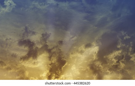 Cloudy sunset sky with sun rays