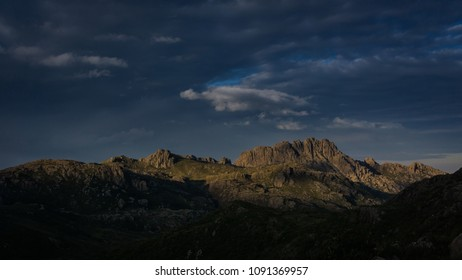 Cloudy sunset, with the sun directly illuminating the Agulhas Negras mountain, which is one of the 10 highest mountains in Brazil. The rocks lit by the sun and the rest already darkened by the shade.