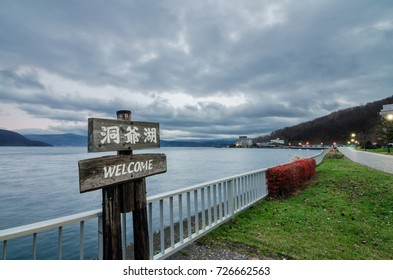 """Cloudy view of the infamous Lake Toya. The lake is a volcanic caldera lake in Shikotsu-Toya National Park, located in Hokkaid, Japan. Text on signboard read as """"Lake Toya"""""""