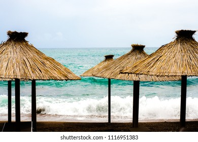 Cloudy weather at the beach with straw parasols