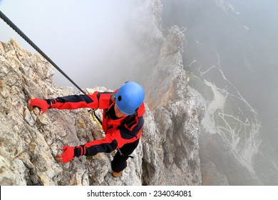 "Cloudy weather and young woman climbs steep ridge on via ferrata ""Punta Ana"", Tofana massif, Dolomite Alps, Italy"