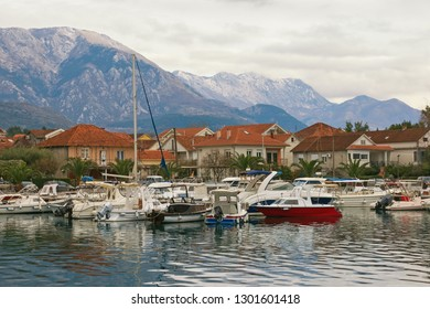 Cloudy winter day. Small marina for fishing boats at the foot of the mountains.   Montenegro, Bay of Kotor. Marina Kalimanj in Tivat city and peaks of Lovcen mountains