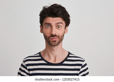 Clouse up of young brunet with beard looking suddenly surprised and discontent, eyebrows raised, lips pursed wears black and white striped tshirt, stands rightside isolated over white background