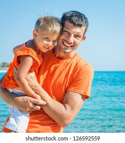 Clouseup portrait of happy father with son laughing and looking at camera on the beach