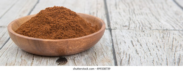 Clove powder in wooden bowl over wooden background