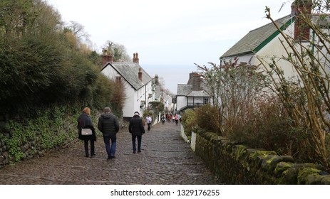 Clovelly, Devon, England, UK.  February 23, 2019.  People descending down the steep, cobbled street towards the centre of the village.