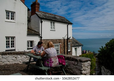 Clovelly, Devon, UK. JULY 2011. A couple enjoying tea at a cafe overlooking the sea on a sunny day at Clovelly harbour in Devon