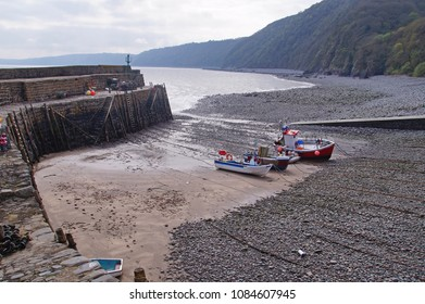 Clovelly which is a small histroic fishing village in Devon, with a small harbour and a few fishing boats during low tide and the coastline in the background