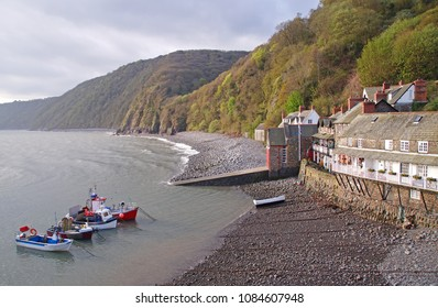 Clovelly which is a small histroic fishing village in Devon, with a small harbour and a few fishing boats during high tide and the coastline in the background
