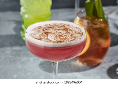 The Clover Club Cocktail is a cocktail consisting of gin, lemon juice, raspberry syrup, and egg white. Red Clover Club Cocktail with white foam and cinnamon powder. Vintage table,  sunshine and shadow - Shutterstock ID 1992496004