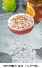 The Clover Club Cocktail is a cocktail consisting of gin, lemon juice, raspberry syrup, and egg white. Red Clover Club Cocktail with white foam and cinnamon powder. Vintage table,  sunshine and shadow - Shutterstock ID 1992496007