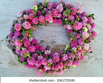 Clover flower pink round wreath frame on wooden background. Medicinal herb clover flowers on round shape wreath on cracked wood table or wall. Old weathered texture wall & clover flowers border wreath