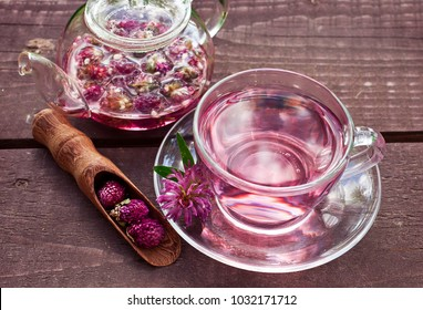 Clover flower tea in the almost empty glass teapot, a glass cup of tea, scoop of dry clover flowers on a wooden table