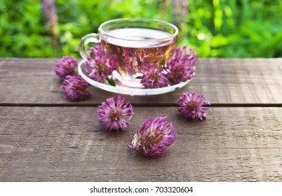Clover flower tea in the glass cups on a wooden table