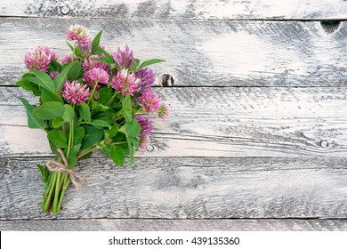 Clover flowers on wooden background. Beautiful wildflower bouquet. Top view.
