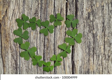 clover heart on wooden background