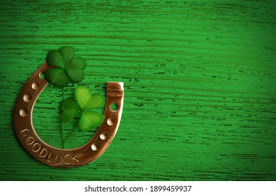 Clover leaves and horseshoe on green wooden table, flat lay with space for text. St. Patrick's Day celebration