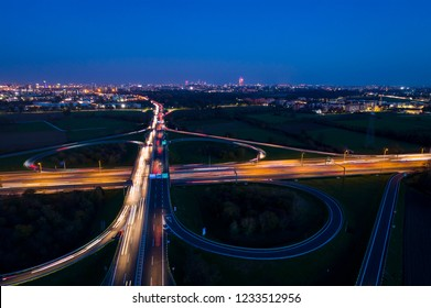 Cloverleaf interchange seen from above. Aerial view of highway road junction in the night with light trails of evening traffic. Bird's eye view. City lights in the background.
