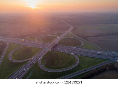 Cloverleaf interchange seen from above. Aerial view of highway road junction in the Po valley near Milan at sunset. Bird's eye view.