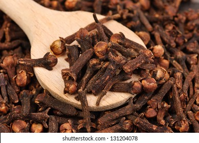 Cloves (spice) and wooden spoon close-up food background - Shutterstock ID 131204078