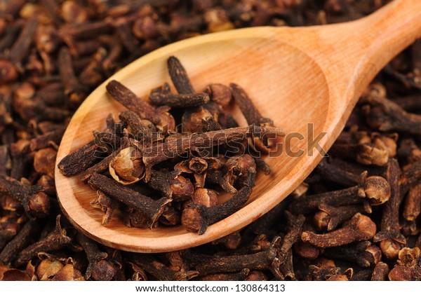Costumes (épices) et cuillère en bois en gros plan sur fond de nourriture