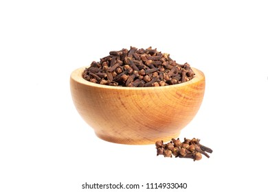Cloves in wooden bowl isolated on white. Whole cloves