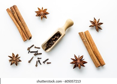 cloves with wooden spoon and cinanmon and star anise on white background