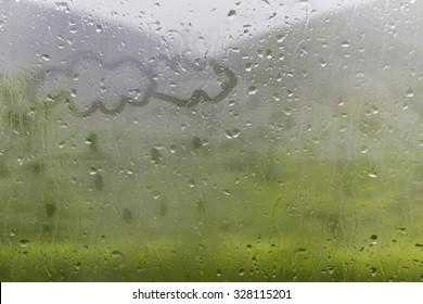Clowds drawn on the foggy glass window on a raining day