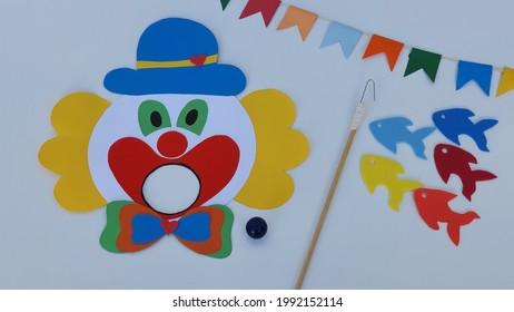 Clown, ball to play in the clown's mouth, toy fishing and colorful flags. White background. One of the traditions to brighten up the Brazilian June party is the Boca do Palhaço and Toy Fishing games.