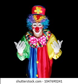 Clown in a black studio making inviting gesture front view portrait