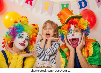 clown girl and clown boy at the birthday of a child. Party for children. Clowns and little girl show different emotions