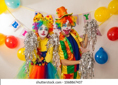 Clown girl and clown boy in bright costumes at the baby's birthday party. The explosion of emotions and the fun of the circus. Paper disco made of silver paper