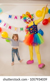 clown girl on the birthday of a child. A party for a child. Emotional Child fools around