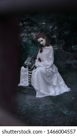 Clown girl in white clothes, sad sitting on the little horse in the center of the frame, shot in natural light.