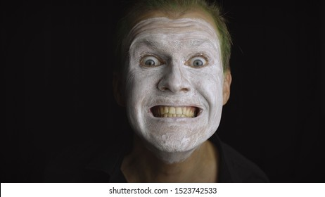 Clown Halloween man portrait. Close-up of an crazy, evil clowns face. White face makeup. Green hair. Scary laugh. Attractive model in Halloween costume. Dark background
