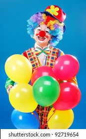 Clown holding balloons over the blue background
