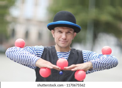 The clown juggles with pink balls on the street of a European city