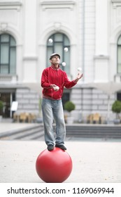 The clown juggles with white balls, standing on a big red ball in the street of a European city