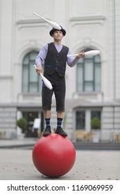 The clown juggles with white maces, standing on a big red ball in the street of a European city