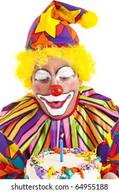 Clown makes a wish and blows out the candle on his birthday cake.