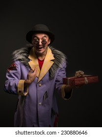 Clown man with Christmas gift box on black background