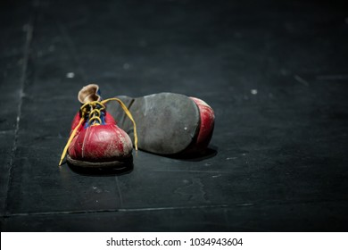 Clown old red shoes isolated on stage. Copy space. Red shoes on a dark background. Concept: Left behind.