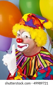 Clown with a secret, holding his finger to his lips.