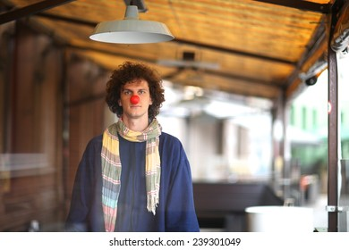 Clown standing at cafe terrace under the lamp