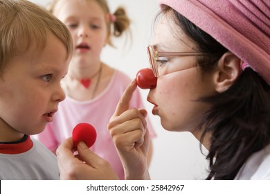 Clown-doctor : boy is watching clown how to put red nose on.