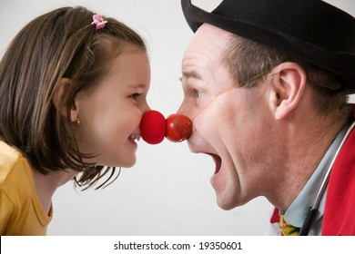 Clown-doctor : red nose contact of clown with kid. Profiles of man and girl.
