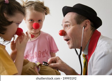 Clown-doctor : two girls and clown with red noses are smiling and joking during medical examination of teddy bear.