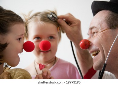 Clown-doctor : two girls and clown with red noses are smiling and joking during medical examination.