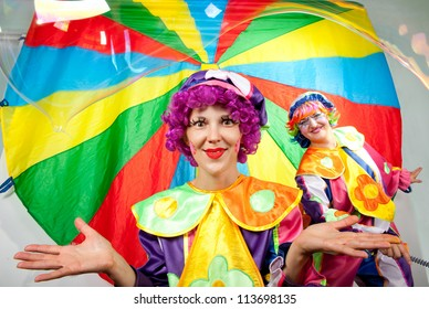 Clowns are making fun with bubbles on colorful background